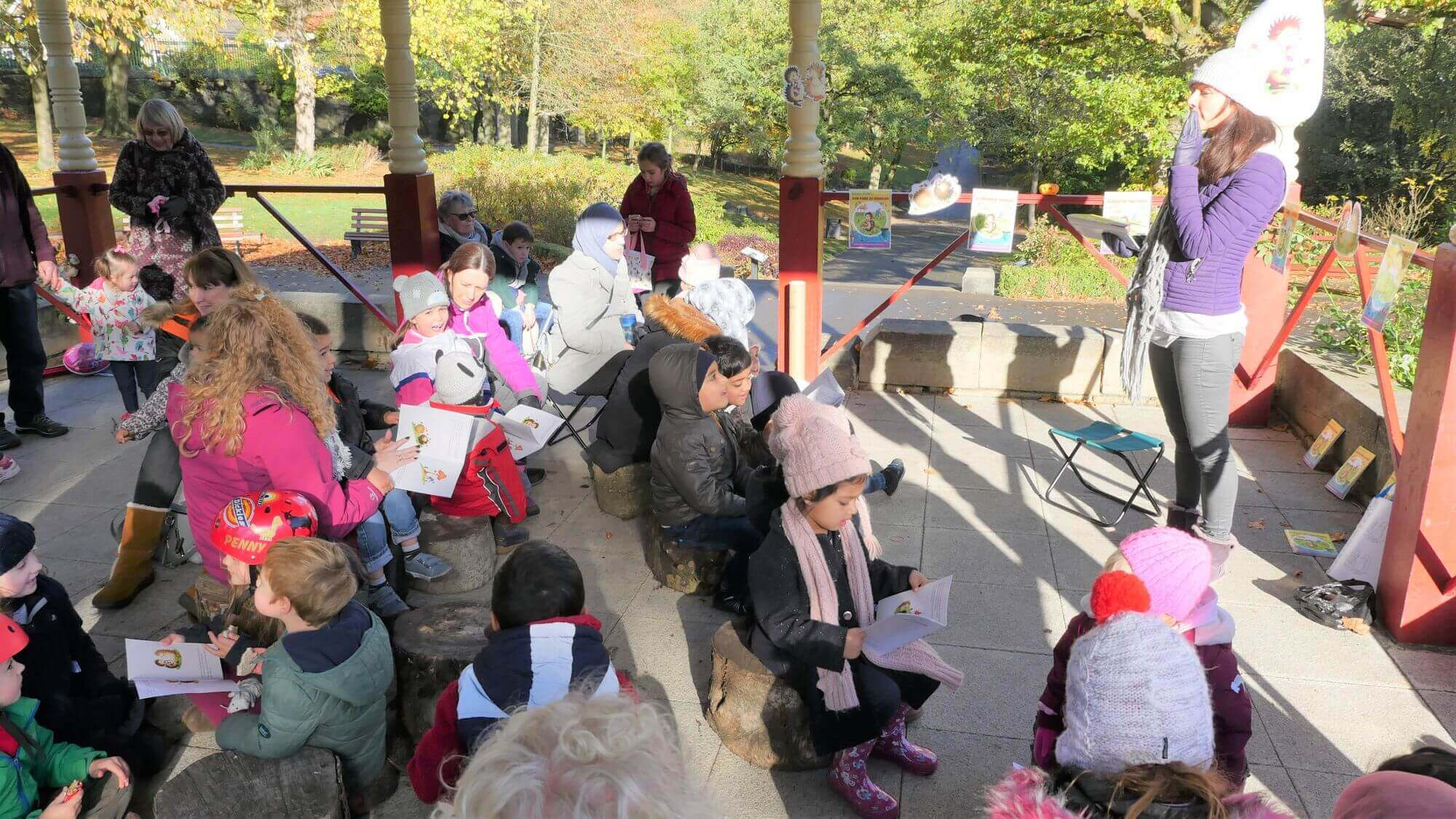 """Claire Culliford reading to children at a """"Hector Helps Clean Up The Park"""" event"""